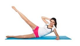 Fêmea nova bonita que exercita em um azul matt Imagens de Stock