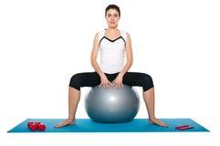 Fêmea nova bonita que exercita em um azul matt Imagem de Stock