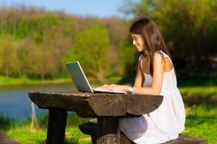 Fêmea nova bonito com um portátil que senta-se no brench fotografia de stock