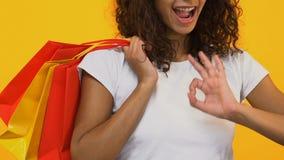 Fêmea nova com os sacos da compra que mostram o sinal aprovado, desconto do boutique, forma vídeos de arquivo