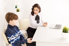 Fêmea nova do brunnette que fala ao menino interno a sala branca Mulher do psicólogo com patiant Terapia da psicologia fotos de stock