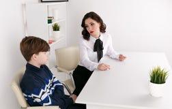 Fêmea nova do brunnette que fala ao menino interno a sala branca Mulher do psicólogo com patiant Terapia da psicologia imagens de stock