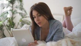 A fêmea nova está usando o dispositivo, encontrando-se na cama no interior home video estoque