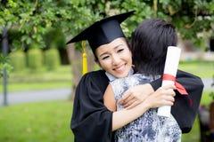 Fêmea nova graduada abraçando seu amigo na cerimônia de graduação fotos de stock