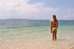 Fêmea nova no biquini que enfrenta o mar, vista larga Imagem de Stock