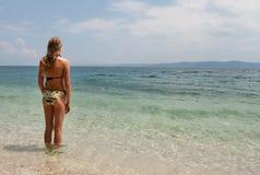 A fêmea nova no biquini que enfrenta o mar, vista larga saiu Fotos de Stock Royalty Free