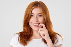 A fêmea nova positiva com pele freckled, mantém o dedo dianteiro perto da boca, sorri amplamente, tem o cabelo avermelhado, tem m fotografia de stock