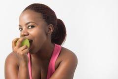 Fêmea nova preta que aprecia sua maçã verde Foto de Stock