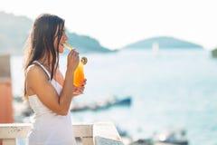 Fêmea nova que aprecia um cocktail colorido no terraço do hotel da vista panorâmica Batido delicioso frio do cocktail Imagem de Stock