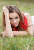 Fêmea nova que encontra-se para baixo na grama Imagens de Stock