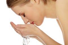 Fêmea nova que lava sua face imagens de stock