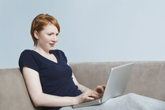 Fêmea nova que olha surpreendentemente no portátil Imagens de Stock Royalty Free
