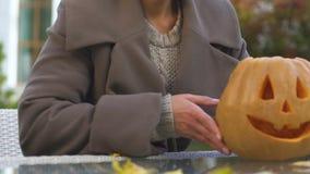 Fêmea nova que põe a abóbora cinzelada de sorriso do jaque sobre a tabela, decorações de Dia das Bruxas video estoque