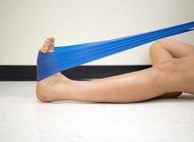 A fêmea nova que usa uma faixa da resistência para o tornozelo exercita no gym fotos de stock royalty free