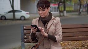 A fêmea nova usa o smartphone ao sentar-se no banco video estoque