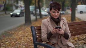A fêmea nova usa o smartphone ao sentar-se no banco filme