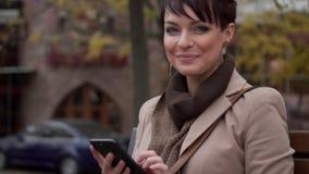 A fêmea nova usa o smartphone ao sentar-se no banco vídeos de arquivo