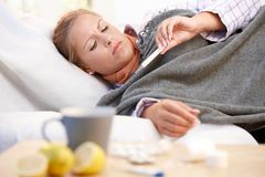 Fêmea novo estando com a gripe colocar na cama imagem de stock royalty free
