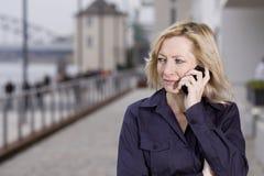 Fêmea ocasional esperta com fala móvel no móbil fotos de stock royalty free
