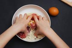 A fêmea ou a menina entregam a fatura da carne triturada que enchem no fundo da mesa de cozinha, vista superior Cozimento, receit fotografia de stock