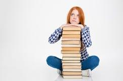 A fêmea pensativa pôs a cabeça sobre a pilha de livros imagem de stock royalty free