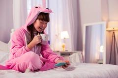 Fêmea pequena moreno feliz que olha o filme favorito fotos de stock