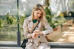 Fêmea preocupada bonita que olha ao relógio, esperando alguém que está dentro atrasado imagem de stock