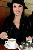 Fêmea que come um copo do chá imagem de stock