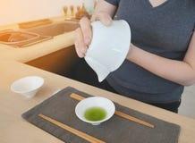 A fêmea que derrama o chá verde ao copo cerâmico pequeno branco no cinza veste a esteira em uma loja do chá imagens de stock royalty free