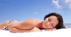 Fêmea que encontra-se para baixo na praia sob o sol do verão Fotos de Stock Royalty Free