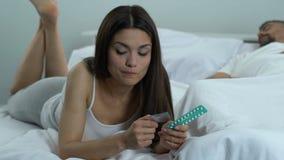 Fêmea que escolhe os comprimidos orais, jogando afastado o preservativo, prevenção da gravidez, saúde video estoque