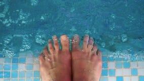 Fêmea que espirra os pés na piscina clara fresca filme