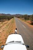 Fêmea que está ao lado do carro que olha abaixo da estrada Fotografia de Stock