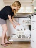 Fêmea que esvazia a máquina de lavar louça Fotos de Stock Royalty Free
