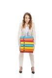 Fêmea que leva pastas pesadas contra Imagem de Stock