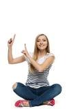 Fêmea que senta-se com pés cruzados no assoalho que aponta acima Imagens de Stock