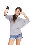 Fêmea que toma imagens dsi mesma no telefone esperto Imagens de Stock Royalty Free