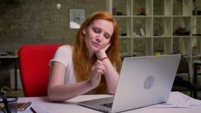 A fêmea ruivo caucasiano de bocejo está olhando a tela do portátil ao sentar-se no escritório do tijolo em desktop, criativo video estoque