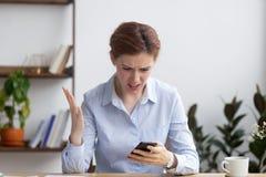 A fêmea sente a irritação sobre o telefone celular descarregado ou quebrado fotografia de stock royalty free