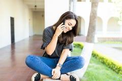 Fêmea tendo a conversação engraçada com o amigo em Smartphone foto de stock royalty free