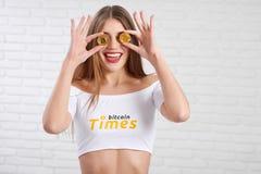 Fêmea tonificada atrativa alegre que guarda dois bitcoins dourados na frente de seus olhos imagens de stock royalty free