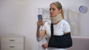 Fêmea triste na mensagem cervical da leitura do estilingue do colar e do braço da espuma no smartphone video estoque