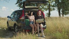 Fêmeas com o mapa que procura o sentido na viagem do carro video estoque