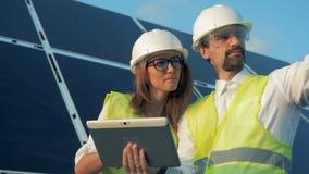 Fêmeas e uns trabalhadores masculinos de uma energética estão discutindo o projeto de construção e estão apontando em sentidos di vídeos de arquivo