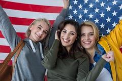 Fêmeas felizes que guardam a bandeira americana atrás de suas partes traseiras Imagens de Stock Royalty Free