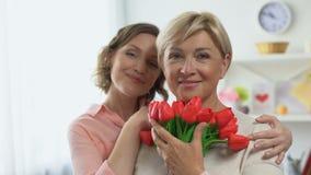 Fêmeas felizes que olham in camera guardando flores da tulipa, dia internacional das mulheres filme