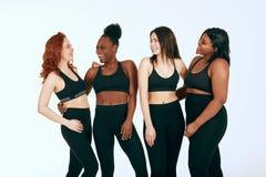 Fêmeas multirraciais com suporte diferente do tamanho e da afiliação étnica junto e sorriso fotografia de stock