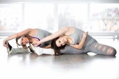 Fêmeas novas desportivas que fazem exercícios para a flexibilidade fotografia de stock