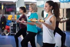 Fêmeas positivas do treinamento diferente da idade com varas ginásticas Imagem de Stock