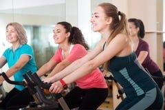 Fêmeas positivas do treinamento diferente da idade em bicicletas de exercício Foto de Stock